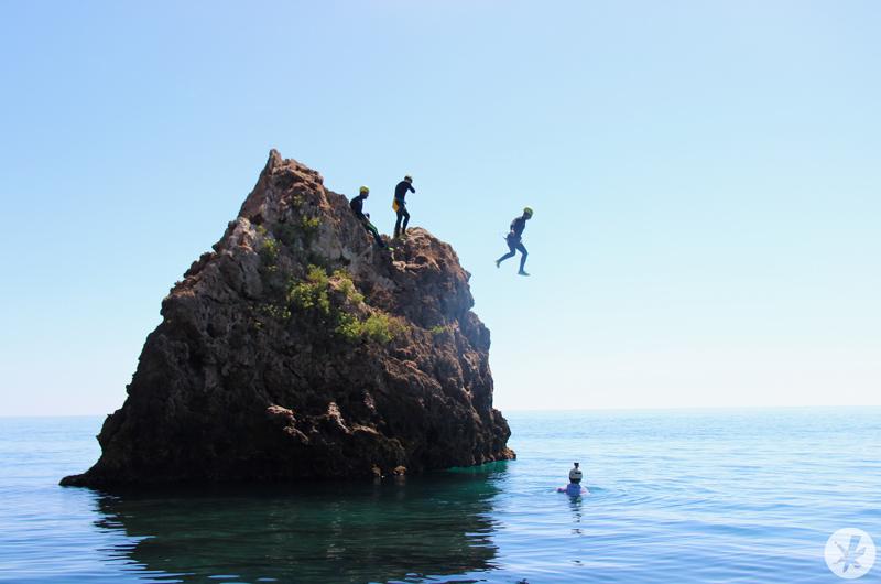 Personas saltando de un acantilado al agua practicando coasteering