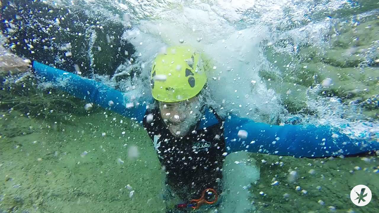 Persona buceando realizando coasteering